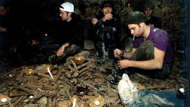 Jugendliche sitzen auf Knochenhaufen und zünden Kerzen an.