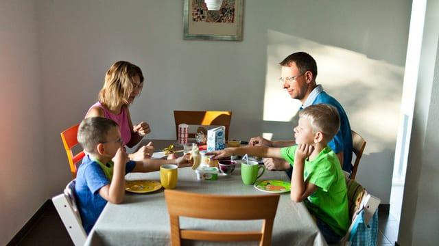 Eine Familie mit zwei Kindern sitzt zum Essen an einem Tisch.