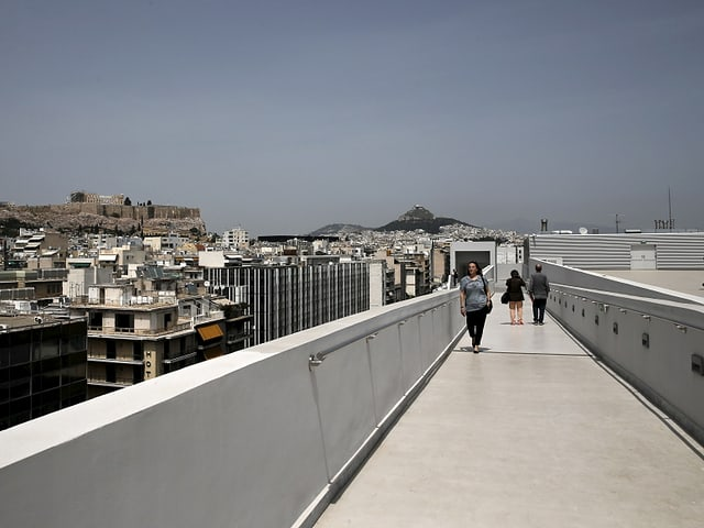 Leute laufen über die Terasse eines Museums in Athen. Im Hintergrund sieht man die Stadt.