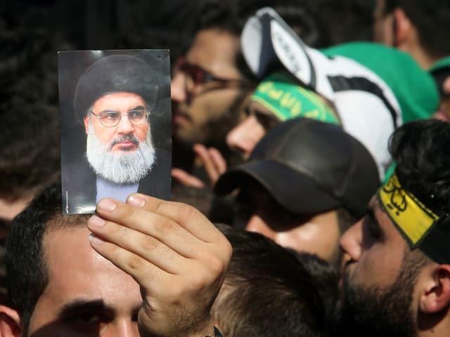 Ein Anhänger hält ein Foto von Nasrallah in die Luft.
