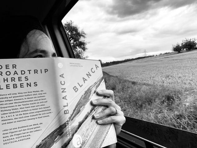 Annette König hält das Buch  «Blanca» von Mercedes Lauenstein in den Händen und schaut aus einem Autofenster hinaus