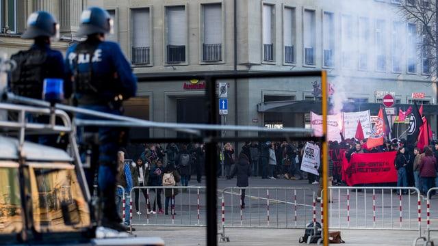 Polizei in Stellung, im Hintergrund ein Demonstrationszug