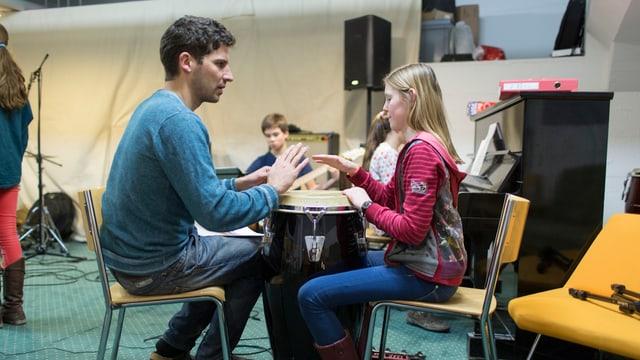 Lehrer am Trommeln mit Schülerin