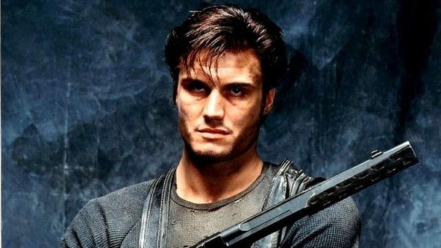 Dolph Lundgren posiert als Punisher mit einer langen Schusswaffe für den gleichnamigen Film.