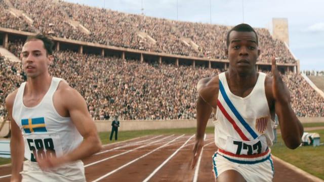 Filmstill: Ein schwarzer und ein weisser Läufer duelleiern sich in einem riesigen Stadion.