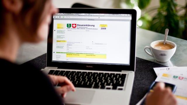 Eine Person sitzt an einem Tisch und füllt am Computer eine Steuererklärung aus.