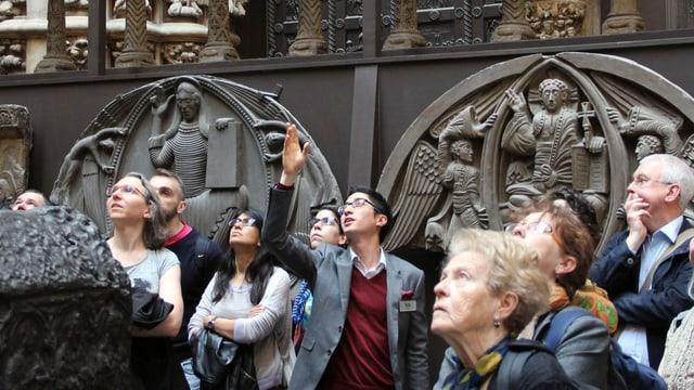 Ein Mann im Jackett zeigt einer Gruppe älterer Menschen Kunst im Victoria & Albert Museum in London.