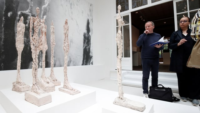 Besucher betrachten dünne, höhe Gipssklupturen.