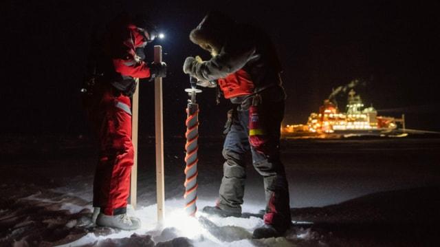 Zwei Forscher in der Dunkelheit. Sie haben einen grossen Eisbohrer. Im Hintergrund das Forschungsschiff.