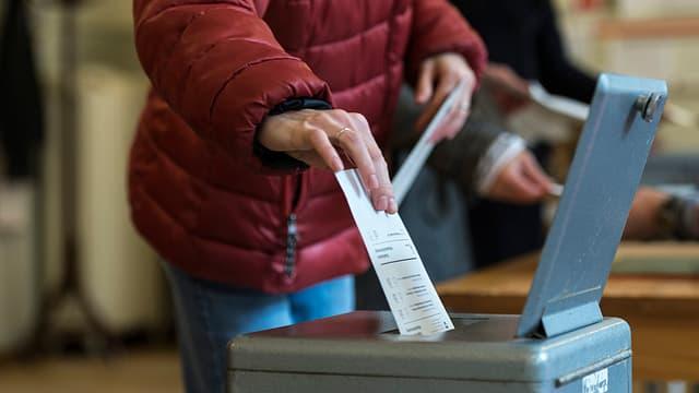 Frau wirft Zettel in Wahlurne