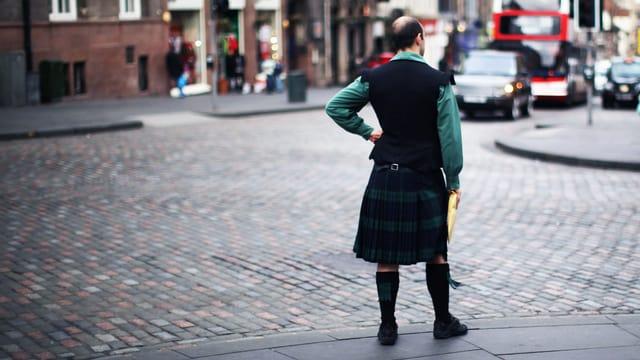 Mann mit in moderner Kleidung und Schottenrock steht an einer Kreuzung.