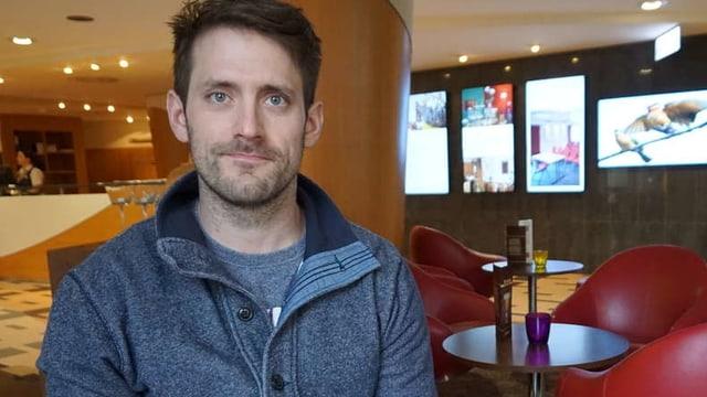 Ein Mann sitzt in einer Cafeteria und schaut in die Kamera