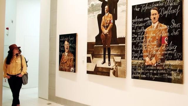 Bilder hängen in einem Ausstellungsraum an einer Wand.
