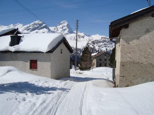 Ein paaer Häuser in einem verschneiten Dorf.