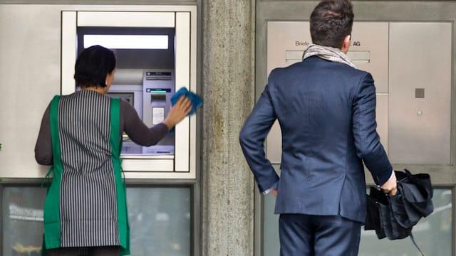 Weibliche Putzkraft reinigt einen Bankomaten, daneben ein Mann in Anzug (beide von hinten)