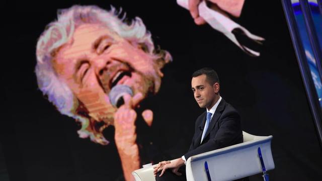 Di Maio sitzt auf einem Stuhl, hinter ihm eine grosse Projektion von Beppe Grillo.