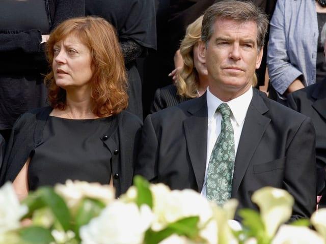 Susan Sarandon als Grace Brewer, Pierce Brosnan als Allen Brewer sitzen in schwarzer Kleidung bei der Beerdigung, im Vordergrund weisse Rosen.