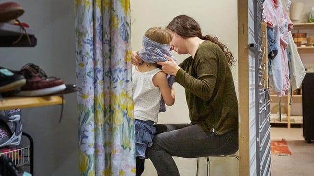 Eine Mutter in einem Brockenhaus mit einem Kind beim Kleider probieren.