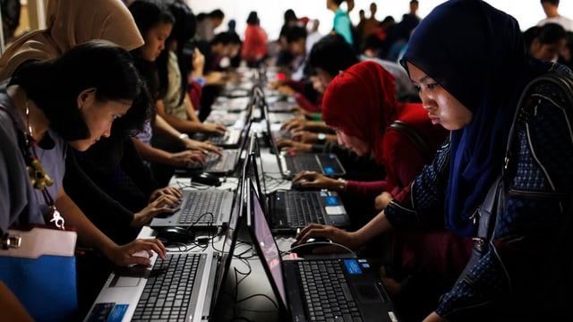 Junge Indonesier und Indonesierinnen füllen an Computern Bewerbungen aus.