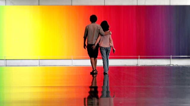 Ein Paar vor einem regenbogenfarbigen Gemälde.