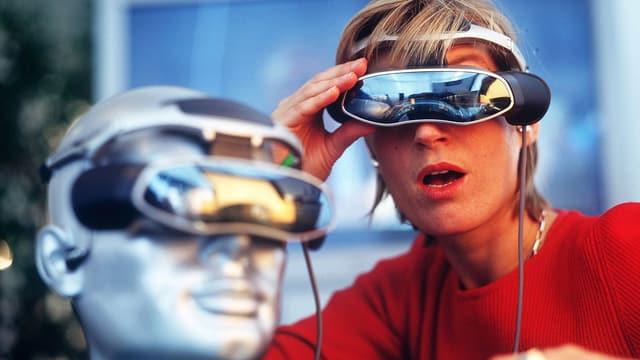 Eine Frau in rotem Pullover schaut durch eine Videobrille.