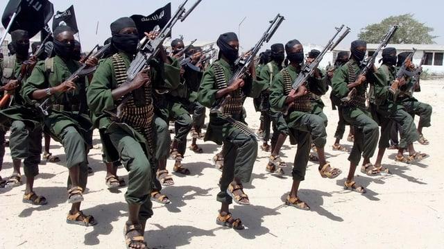 Kämpfer in Uniform mit Patronengürtel und schwarzen Tüchern um den Kopf exerzieren in der Wüste.