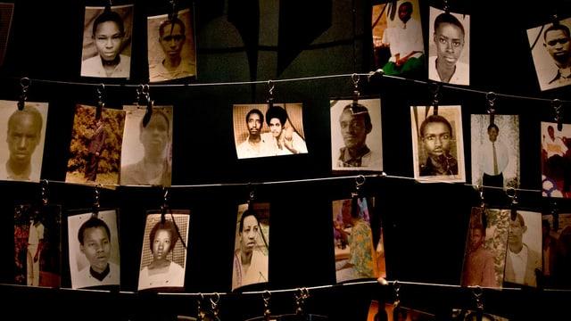 Fotos von Kriegsopfern hängen nebeneinander an Schnüren.