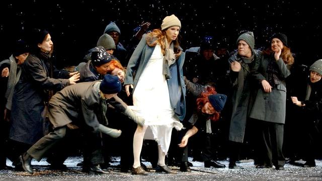 Eine Frau steht mit Mütze auf der Bühne, einige Umstehende zupfen an ihrem weissen Kleid.
