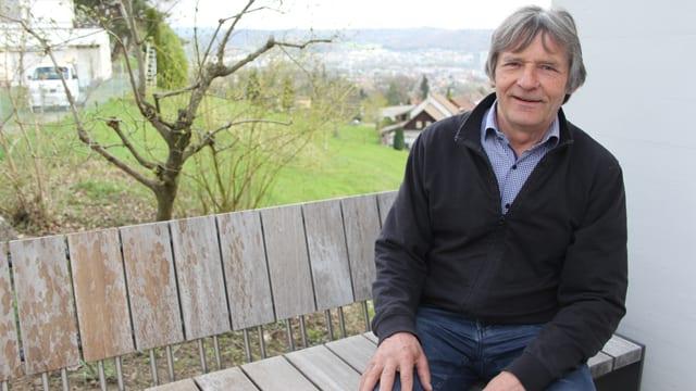 Mann sitzt auf einer Bank, dahinter eine Wiese und Häuser.