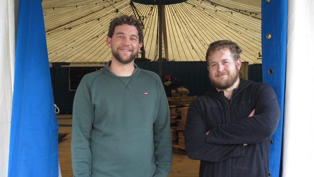 Zwei junge Männer am Eingang zu einem Zirkuszelt.