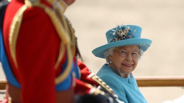 Eine lächelnde Queen in einer Kutsche.