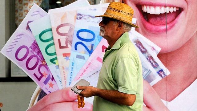 Ein Mann geht an einem Poster vorbei, auf dem eine Werbung mit Euro-Noten zu sehen ist.