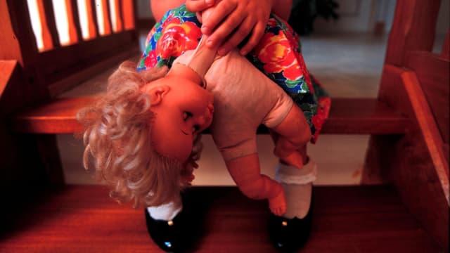 Mädchen sitzt auf einer Treppe mit einer Puppe in der Hand.