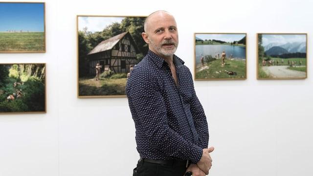 Ein MAnn steht vor Bildern mit Schweizer Motiven.