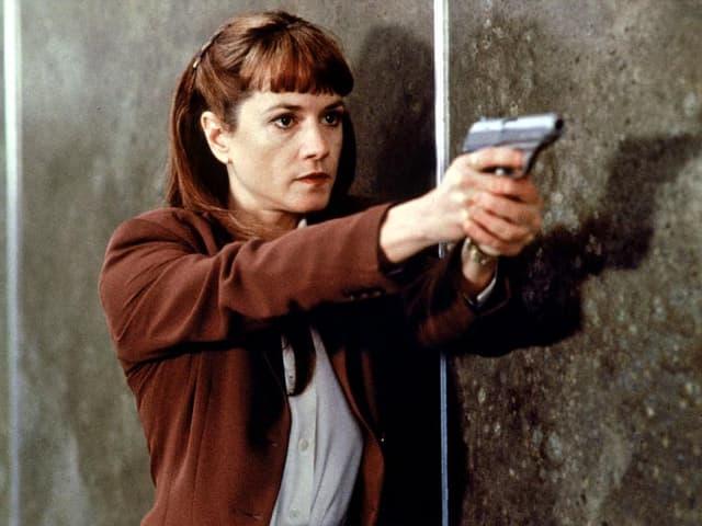 Eine Frau zielt mit einer Pistole.