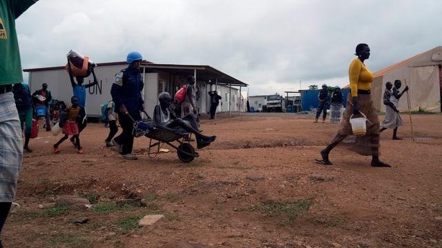 Ein Blauhelmsoldat schiebt eine Schubkarre in der ein Afrikaner sitzt.