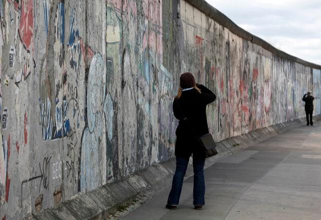Eine Frau fotografiert die Berliner Mauer.