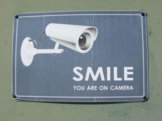 Ein Schild, das draussen an einer Wand hängt. Darauf steht: «Smile. You are on camera.»