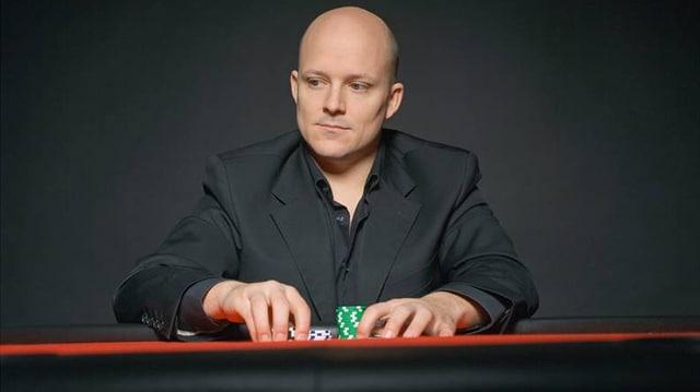 Rino Mathis in einem schwarzen Anzug mit Poker Chips in der Hand.