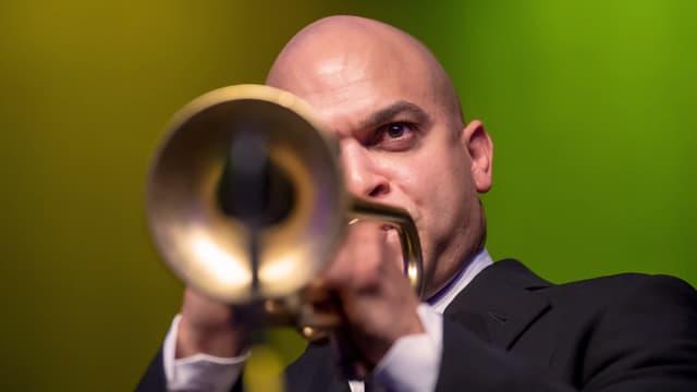 Ein Mann im Anzug spielt Trompete. Das Instrument zeigt mit seiner Öffnung direkt in die Kamera.