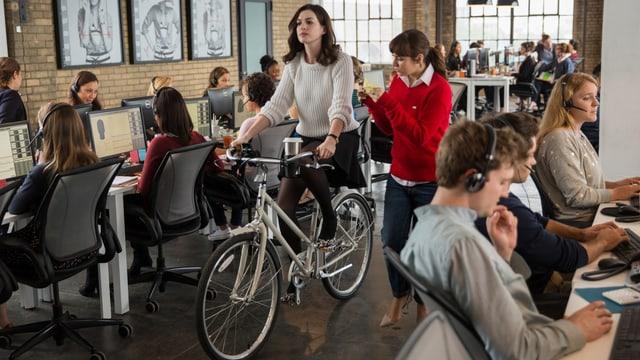 Frau fährt mit Fahrrad durch ein Büro.