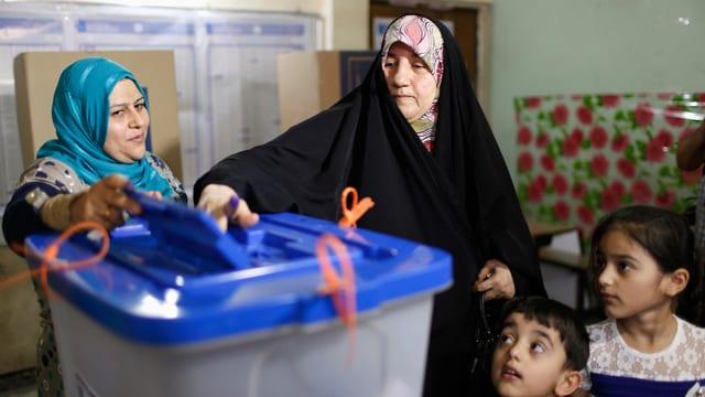 Eine Frau wirft ihren Wahlzettel in die Urne, daneben steht eine Wahlhelferin, an der Seite der Wählerin zwei Kinder.