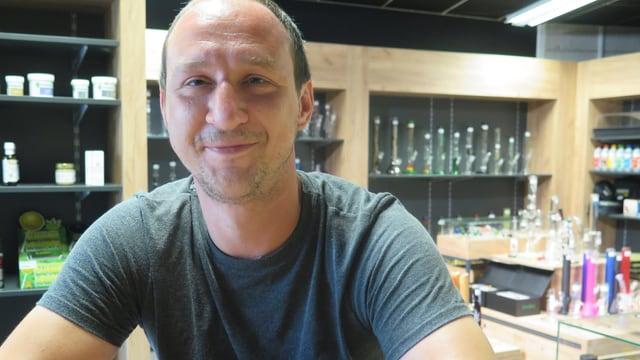 CBD-Shop-Betreiber sitzt in seinem Shop an einem Tisch. Im Hintergrund sind verschiedene Raucherprodukte zu sehen.