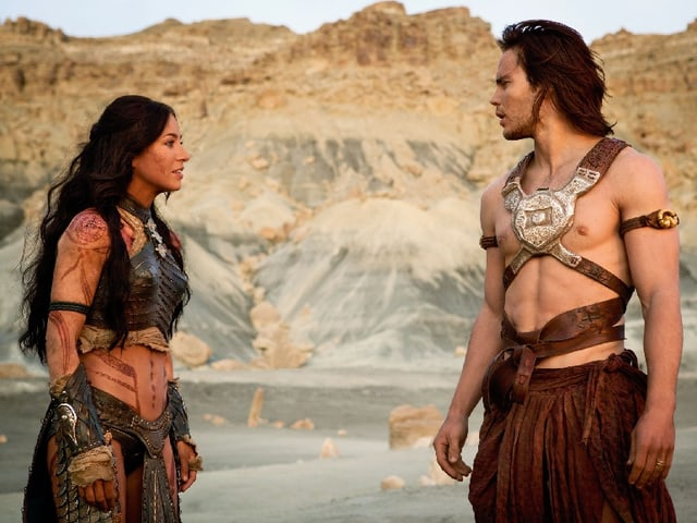 Eine Frau und ein Mann stehen vor einem Steinfelsen.