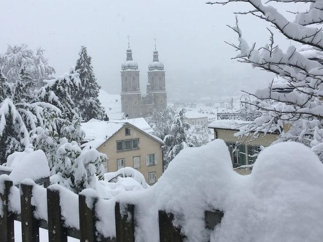 Blick über verschneiten Zaun zum St. Galler Dom, alles liegt unter einem dicken Schneekleid.