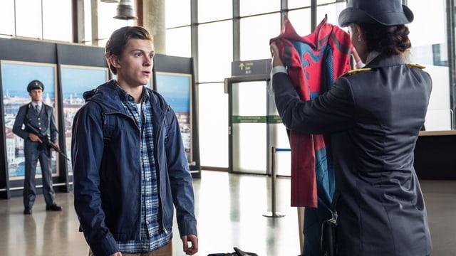 Eine Zollbeamtin hält einen Superhelden-Anzug hoch. Vor ihr steht ein geschockt dreinblickender Teenager..