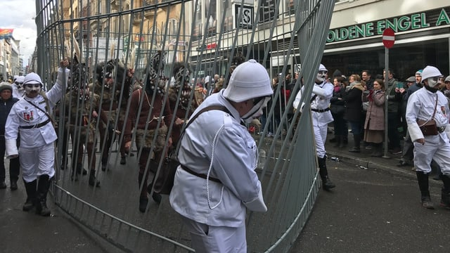 Fasnachtsumzug mit weissen Kolonialbeamten und «Wilden» im Käfig.