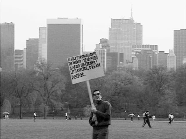 Ein Mann hält ein Schild hoch