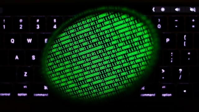 Ein Spiegel reflektiert einen Computerbildschirm auf einer Tastatur. Auf der Spiegelung sind binäre Codes.