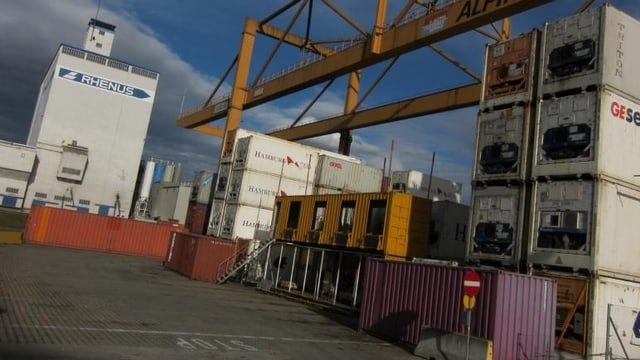 Aufgeschichtete Container, links ein weisses Gebäude